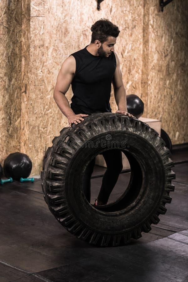 Uomo di forma fisica di sport che lancia addestramento di Crossfit della gomma della ruota immagini stock