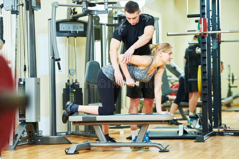 Uomo di forma fisica training L'istruttore personale lavora con la donna immagine stock