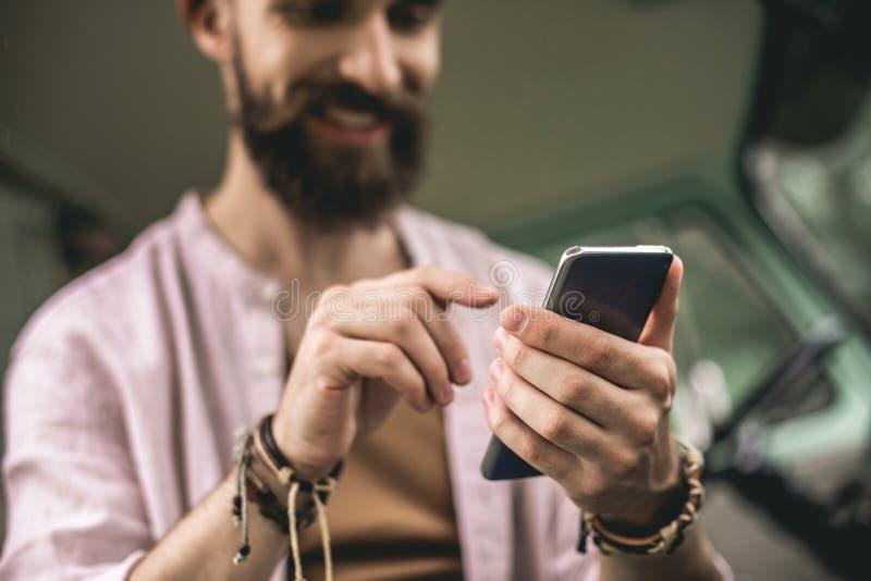 Uomo di hipster felice sorridente con un cellulare fotografia stock libera da diritti