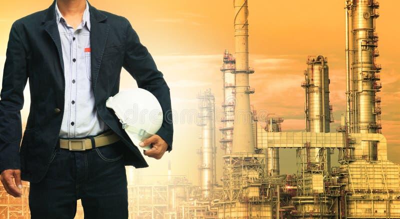 Uomo di ingegneria e casco di sicurezza che sta contro la raffineria di petrolio immagine stock