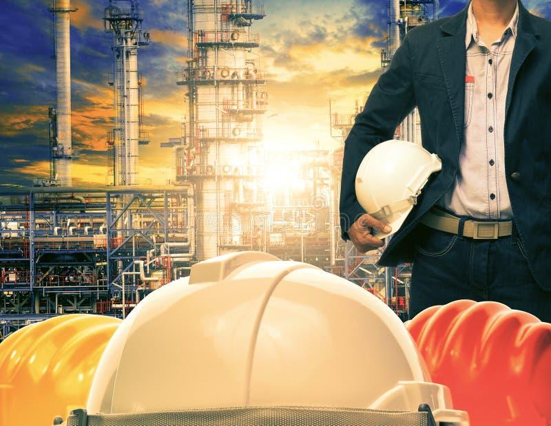Uomo di ingegneria e casco di sicurezza contro il industrie della raffineria di petrolio fotografia stock libera da diritti