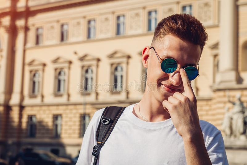 Uomo di istituto universitario bello che controlla i suoi vetri contro l'università Studente felice del tipo con sorridere dello  immagine stock libera da diritti
