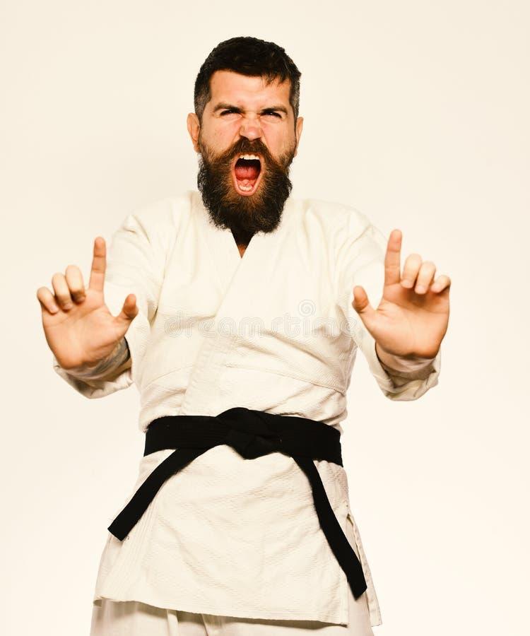 Uomo di karatè con il fronte arrabbiato in uniforme Orientale mette in mostra il concetto Padrone di Jiu Jitsu con la cintura ner fotografia stock
