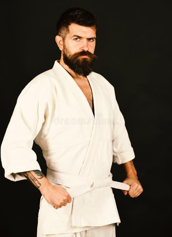 Uomo di karatè con il fronte serio e sicuro in uniforme Uomo con la barba in kimono bianco su fondo nero immagini stock
