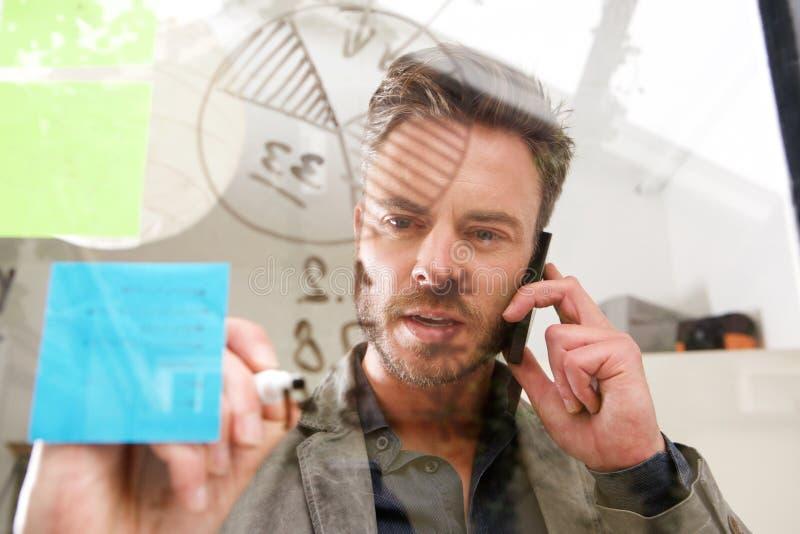 Uomo di medio evo su scrittura del telefono sul bordo di idea immagine stock libera da diritti