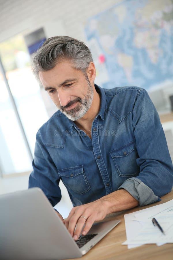 Uomo di mezza età che lavora al computer portatile fotografia stock libera da diritti