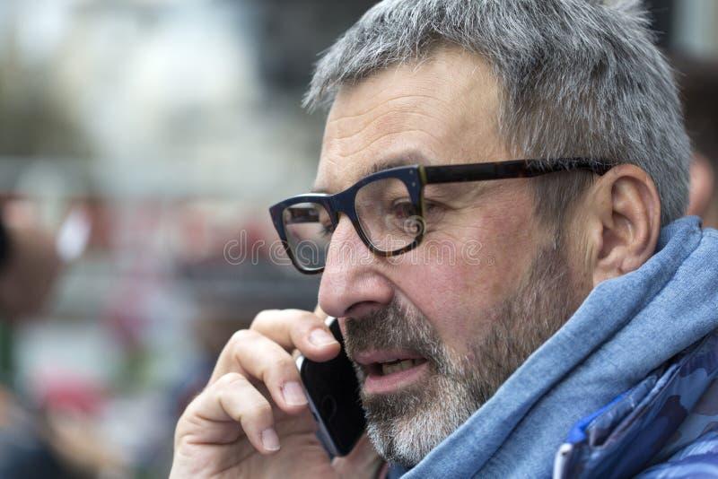 Uomo di mezza età con una barba grigia ed i vetri che parla su un cellulare e che guarda lateralmente fotografie stock
