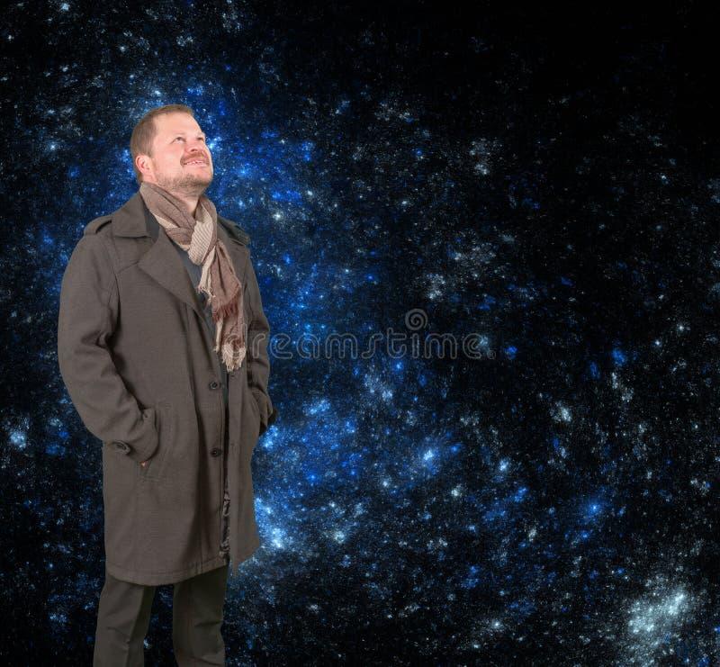 Uomo di mezza età in un cappotto che cerca sul fondo stellato dell'universo fotografie stock libere da diritti