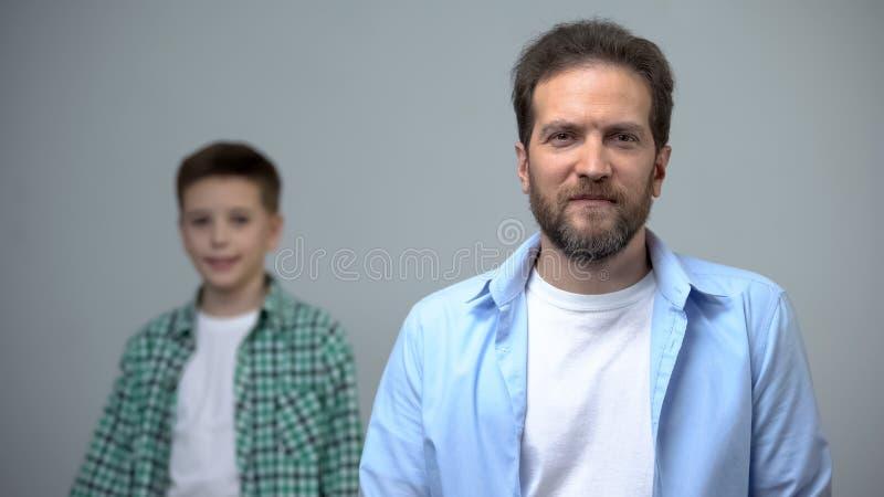 Uomo di mezza et? che sorride al ragazzino della macchina fotografica che sta dietro, memorie di infanzia fotografia stock libera da diritti