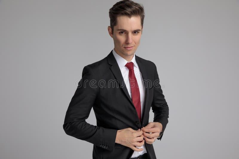 Uomo di modo in vestito nero che abbottona il suo rivestimento di salotto fotografie stock