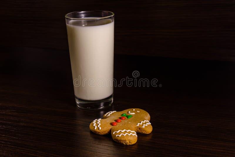 Uomo di pan di zenzero e un bicchiere di latte su una tavola di legno scura fotografia stock