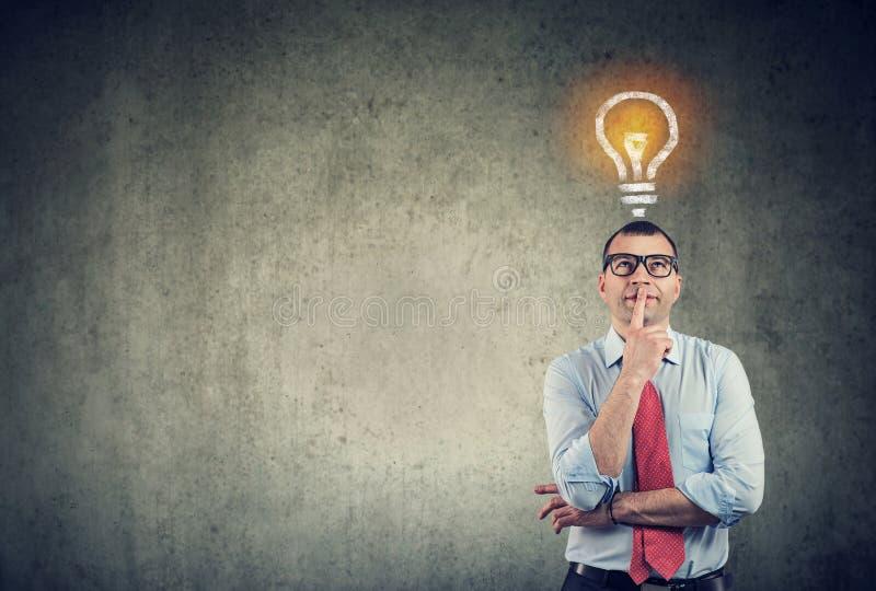 Uomo di pensiero di affari che cerca la lampadina della luce intensa sopra la testa fotografia stock