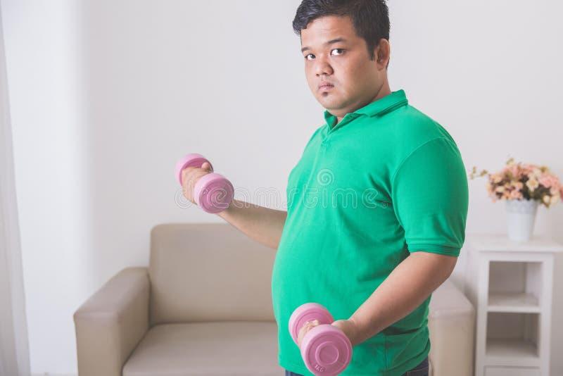 Uomo di peso eccessivo che fa esercizio a casa, alzando una testa di legno a immagini stock libere da diritti