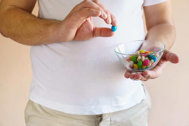 Uomo di peso eccessivo che fa un spuntino mangiando le caramelle zuccherate immagini stock libere da diritti