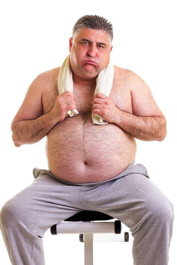 Uomo di peso eccessivo che riposa su un banco per i abdominals, stanco dopo il TR immagine stock