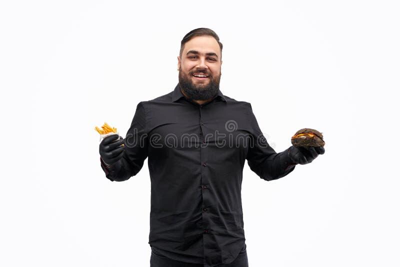 Uomo di peso eccessivo felice con l'hamburger e le patate fritte fotografia stock