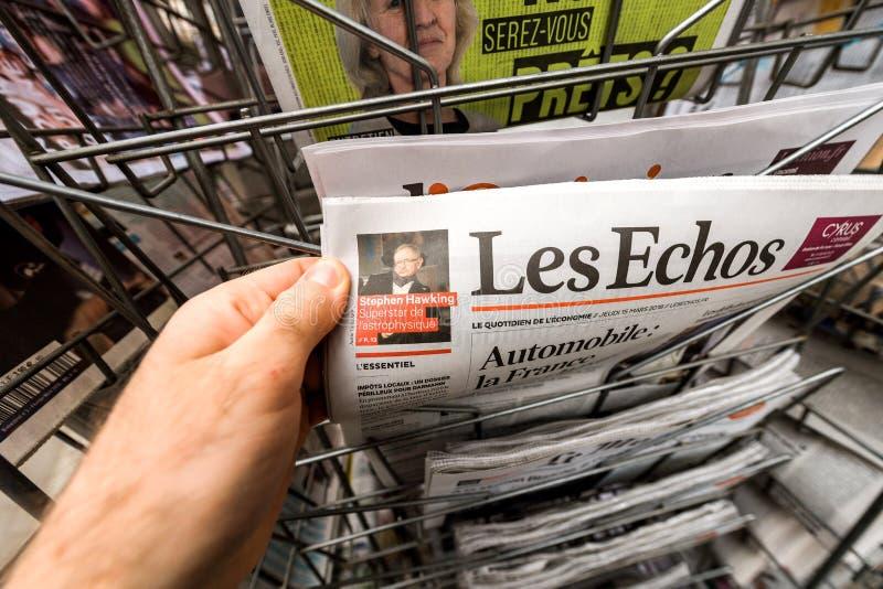 Uomo di POV che tiene il giornale di Les Echos con il portra di Stephen Hawking fotografie stock libere da diritti