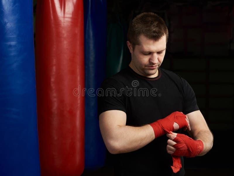 Uomo di pugilato che applica la fasciatura della mano fotografia stock libera da diritti