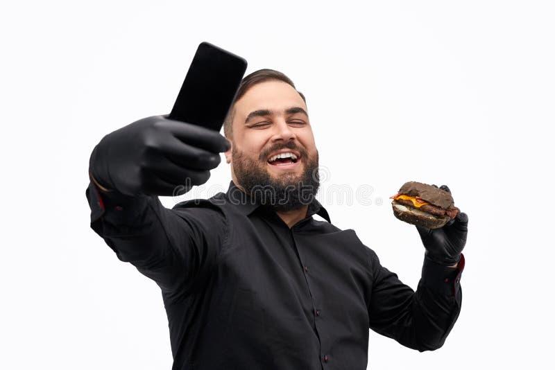 Uomo di risata che prende selfie con l'hamburger fotografia stock