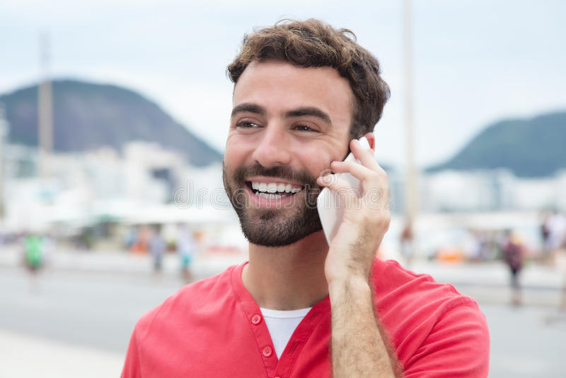 Uomo di risata con la camicia rossa al cellulare nella città fotografie stock
