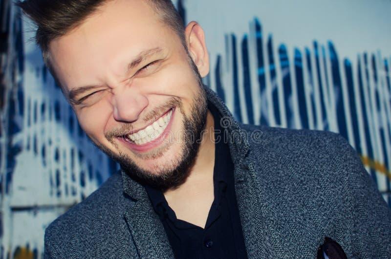 Uomo di risata positivo con un sorriso bianco del dente sui precedenti fotografia stock libera da diritti