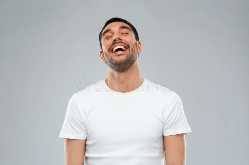 Uomo di risata sopra fondo grigio fotografia stock libera da diritti