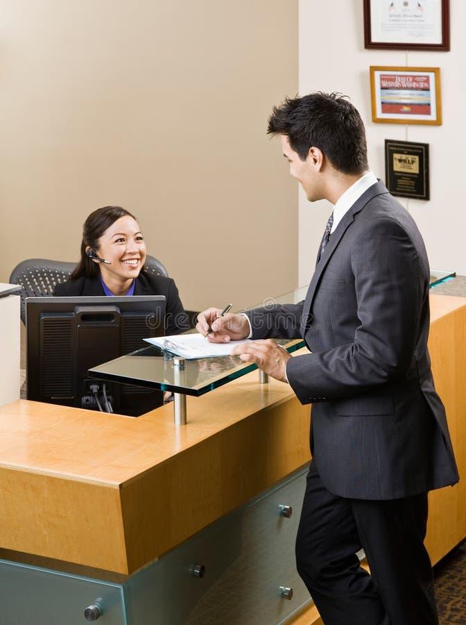 Uomo di saluto del receptionist allo scrittorio di fronte fotografie stock