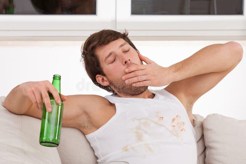 Uomo di sbadiglio con birra fotografia stock