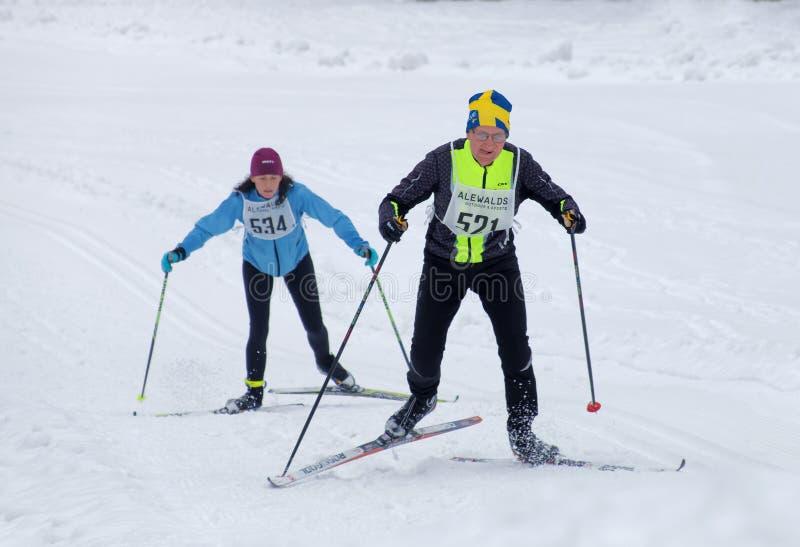 Uomo di sci di fondo che indossa cappello svedese e donna che sciano su fotografia stock libera da diritti