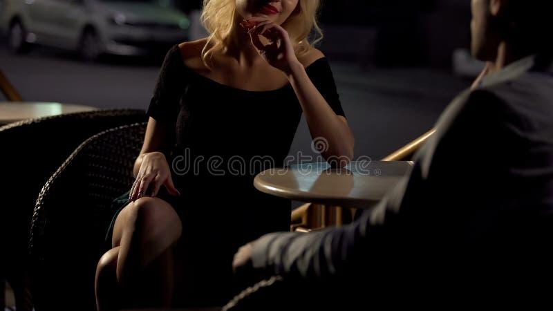 Uomo di seduzione femminile biondo attraente sul terrazzo del ristorante, servizio di scorta immagini stock libere da diritti