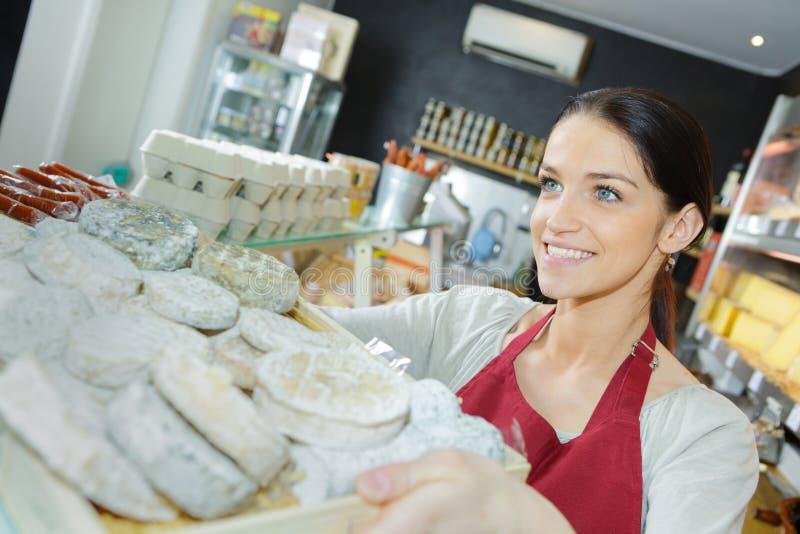 Uomo di Selling Cheese To della venditora in drogheria fotografia stock