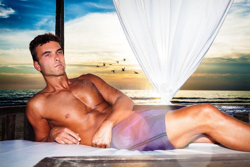 Uomo di serenità che si rilassa su un letto del baldacchino alla spiaggia di tramonto immagini stock libere da diritti