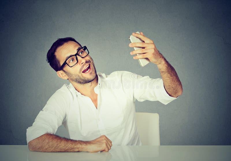 Uomo di sguardo divertente che prende ad immagini di lui auto con lo Smart Phone immagine stock