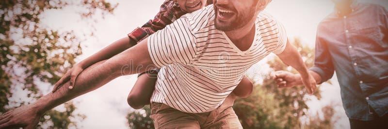 Uomo di sguardo di prima generazione felice che dà trasporto sulle spalle al figlio immagini stock