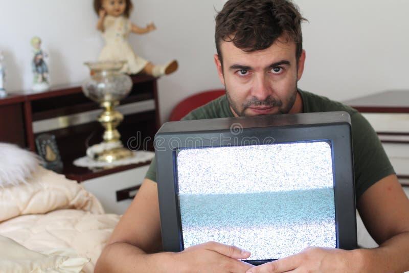 Uomo di sguardo spaventoso che tiene il monitor d'annata della TV fotografia stock libera da diritti
