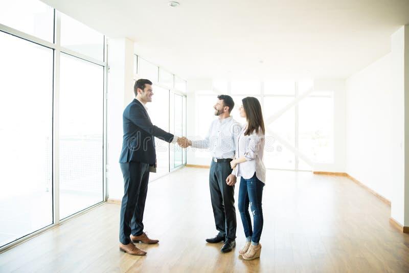 Uomo di Shaking Hands With dell'agente dalla donna nella nuova casa immagine stock