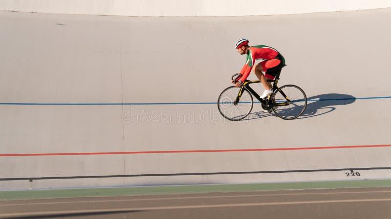 Uomo di sport che cicla sulla pista di sport all'aperto immagine stock libera da diritti