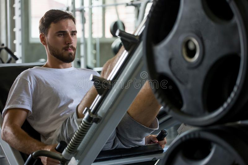 uomo di sport che fa gli esercizi con la macchina della stampa della gamba nella palestra di forma fisica workout Addestramento fotografia stock libera da diritti