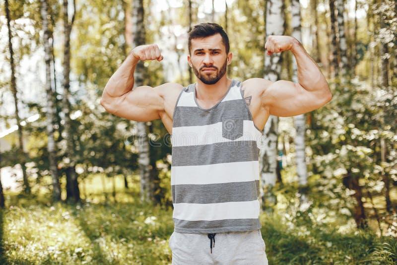 Uomo di sport in un parco di estate di mattina fotografia stock libera da diritti