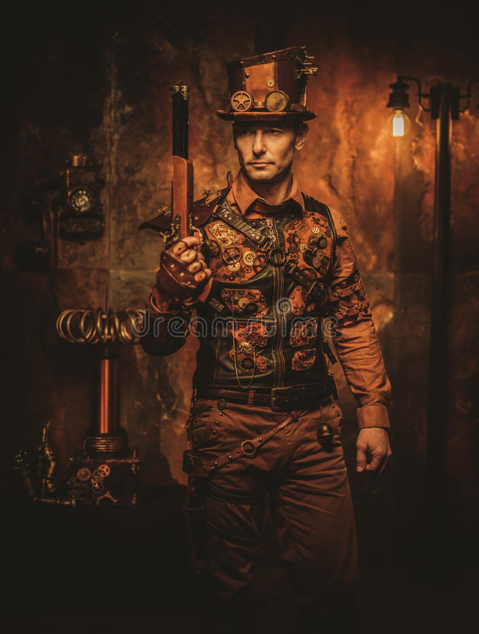 Uomo di Steampunk con la pistola sul fondo d'annata dello steampunk fotografie stock libere da diritti