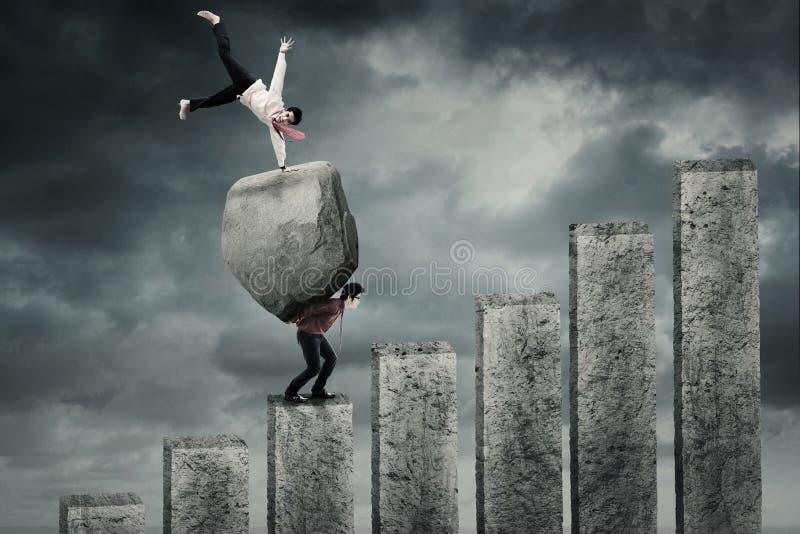 Uomo di successo con roccia e partner immagine stock