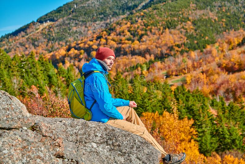 Uomo di viaggiatore con zaino e sacco a pelo al bluff dell'artista in autunno fotografie stock