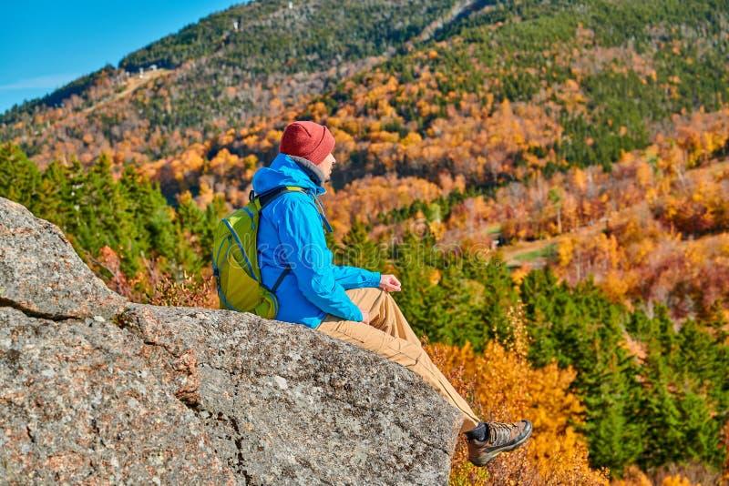 Uomo di viaggiatore con zaino e sacco a pelo al bluff dell'artista in autunno fotografia stock