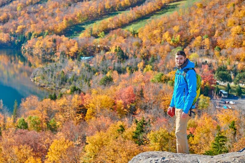 Uomo di viaggiatore con zaino e sacco a pelo al bluff dell'artista in autunno immagine stock libera da diritti