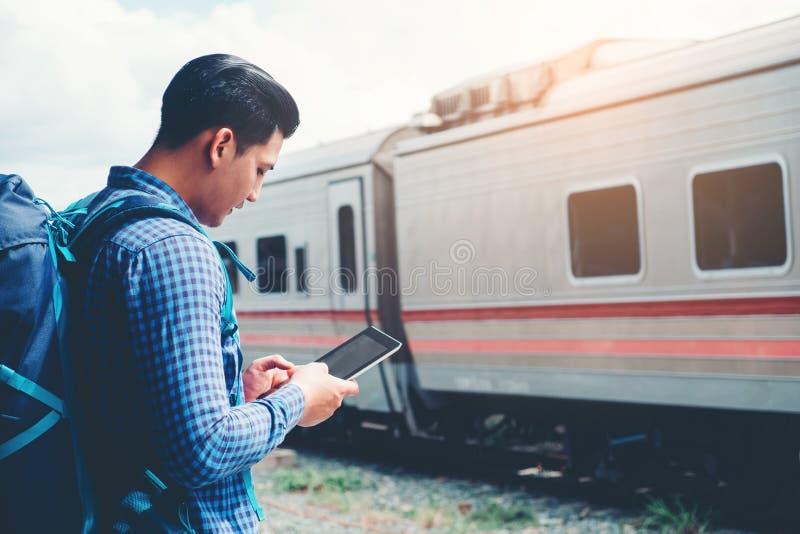 Uomo di viaggio che per mezzo del telefono cellulare al concetto di viaggio della stazione ferroviaria fotografia stock