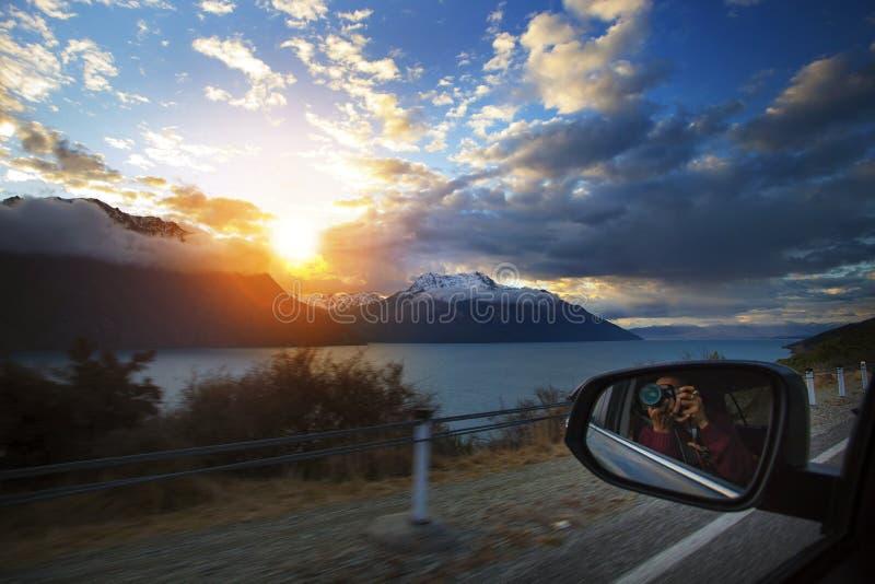 Uomo di viaggio che prende fotografia di tramonto mentre guida di veicoli sul cou fotografie stock