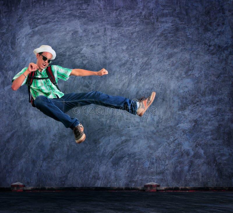 Uomo di viaggio che salta metà di aria con emozione emozionante contro il ceme fotografia stock libera da diritti
