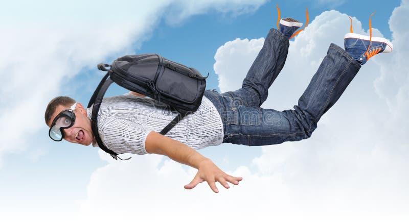 Uomo di volo con la cartella (paracadute) in nubi immagini stock libere da diritti