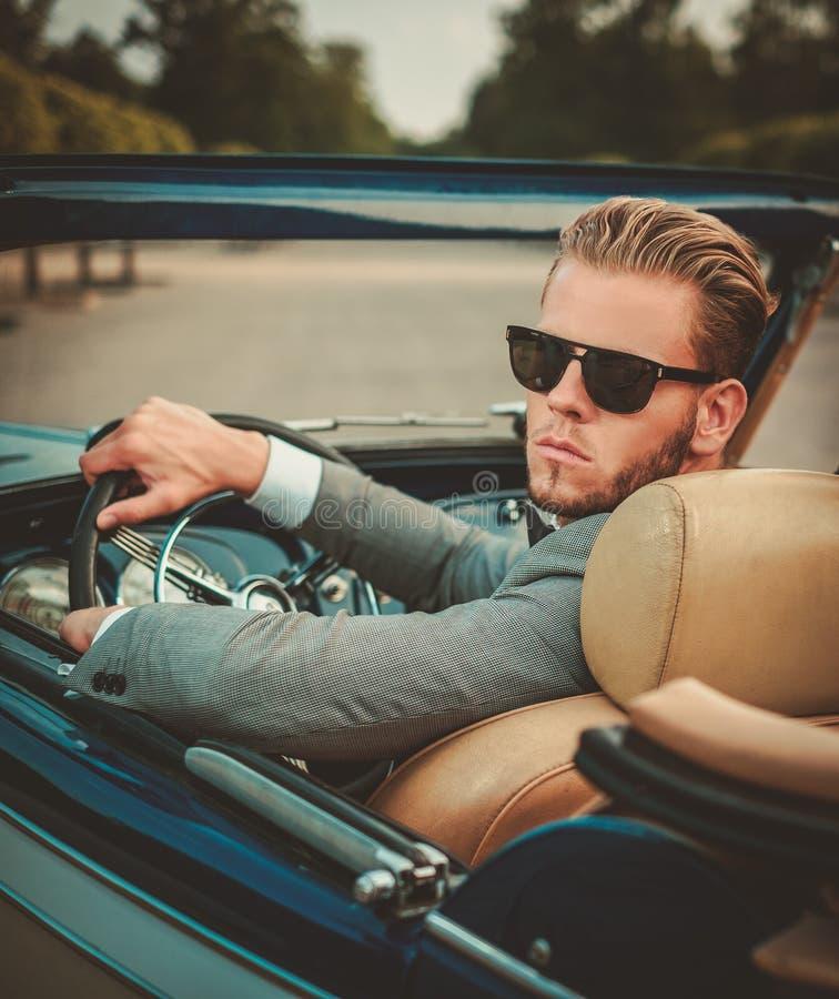 Uomo dietro il volante convertibile classico fotografia stock