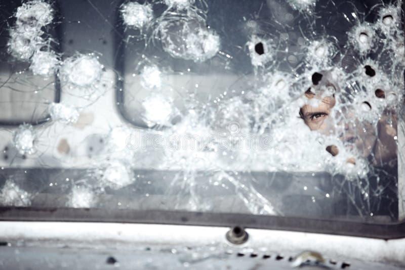 Uomo dietro vetro rotto fotografia stock